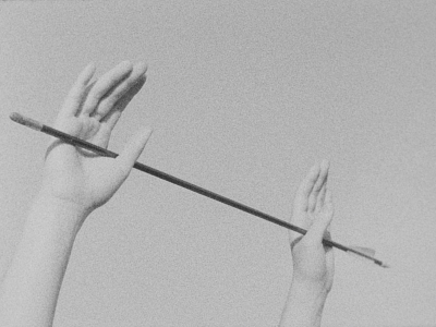 Still from Katelyn Auger's PARADISE IN THE PINES, depicting 2 upraised hands holding an arrow
