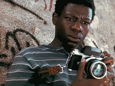 Image of young man holding a camera, from CITY OF GOD (2002)